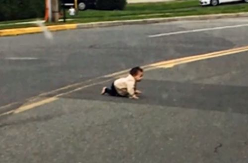 Driver helps rescue baby crawling across road