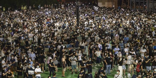 Photos show thousands of Hong Kongers defying a police order to attend vigils memorializing the victims of the Tienanmen Square massacre