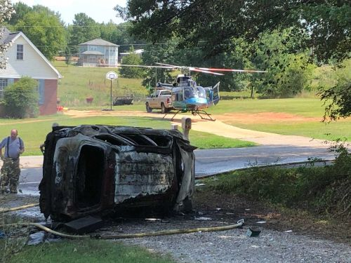 Woman ejected during crash, vehicle lands in driveway, catches fire, officials say