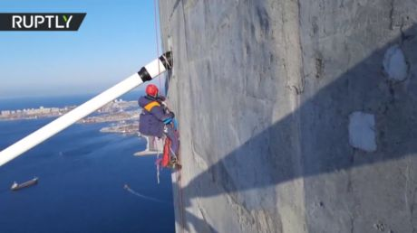 Watch as daring alpinist cleans 320m-high Russky Bridge after freak storm glazes it with ice