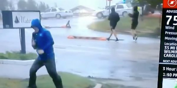 'So dramatic!': Weather Channel reporter braces himself during Florence as two men casually stroll by in viral clip