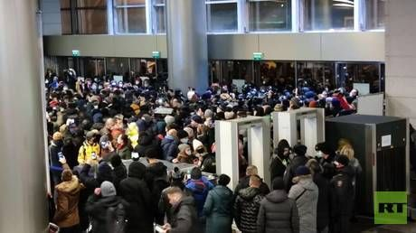 Riot police push crowd out of Moscow airport as opposition figure Navalny expected to land in Russia