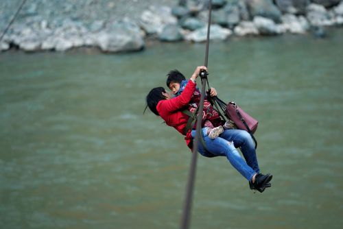 Chinese mountain dwellers take zipline over rapids to run errands