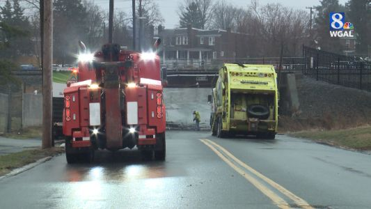 Trash truck hits bridge