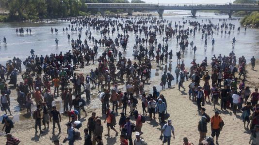 Migrant Caravan Crosses River into Mexico In Standoff With Security Forces