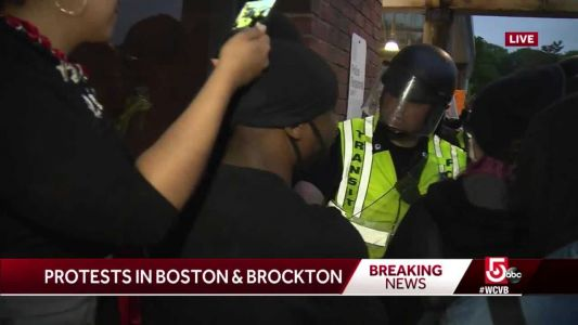 Protester shakes hands with Boston police officer during tense demonstration