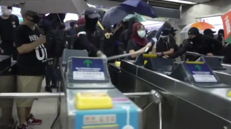 Masked Hong Kong protesters SMASH UP metro station with metal bars and hammers in defiance of emergency order