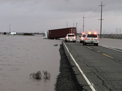 Whoa! Big rig's front end, car swallowed by street flooding