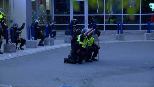 Crowd cheers as Boston officers 'Take a Knee' outside police HQ