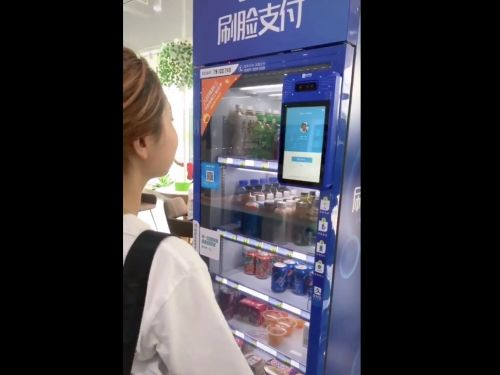 A futuristic Chinese TikTok video shows a woman paying for vending machine items with no money or card - just her face