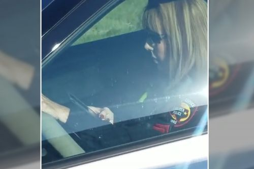 Watch an officer engrossed by her phone while driving