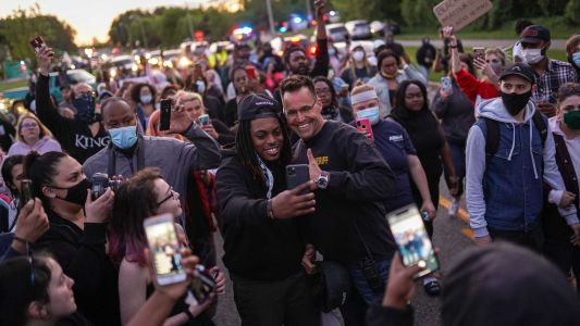 A sheriff put down his baton to listen to protesters. They chanted 'walk with us,' so he did