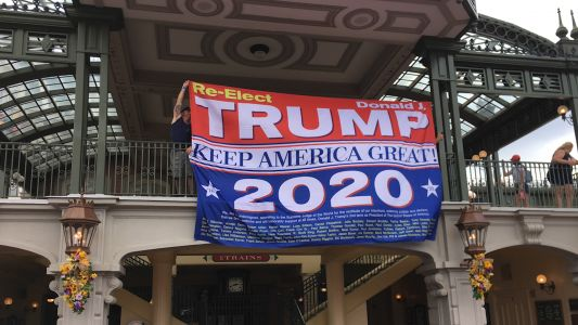 Man hangs Trump re-election banner at Disney World