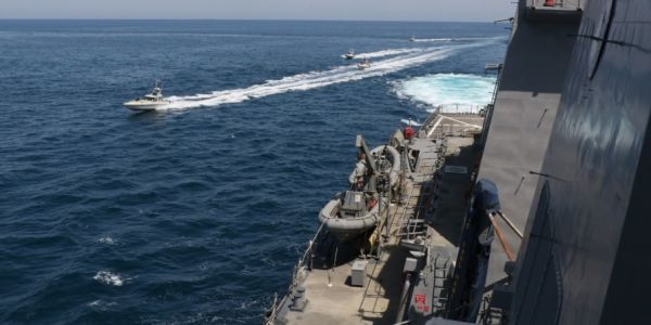 A US Coast Guard ship fired 30 warning shots from a machine gun during an 'unsafe' encounter with Iranian fast-attack boats