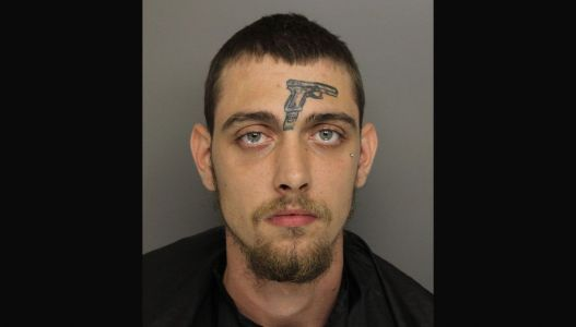 Man with gun tattoo on forehead arrested on gun charge in Greenville, police say
