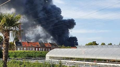 Massive column of smoke visible for MILES as huge fire rages through warehouse in northern France